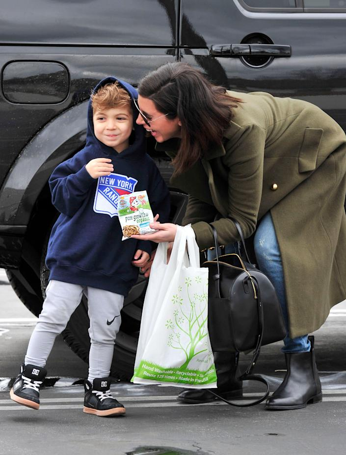 Jamie Lynn Sigler and son with a bag of Pure Growth Organic Snack Mix at aWalmart in Los Angeles.