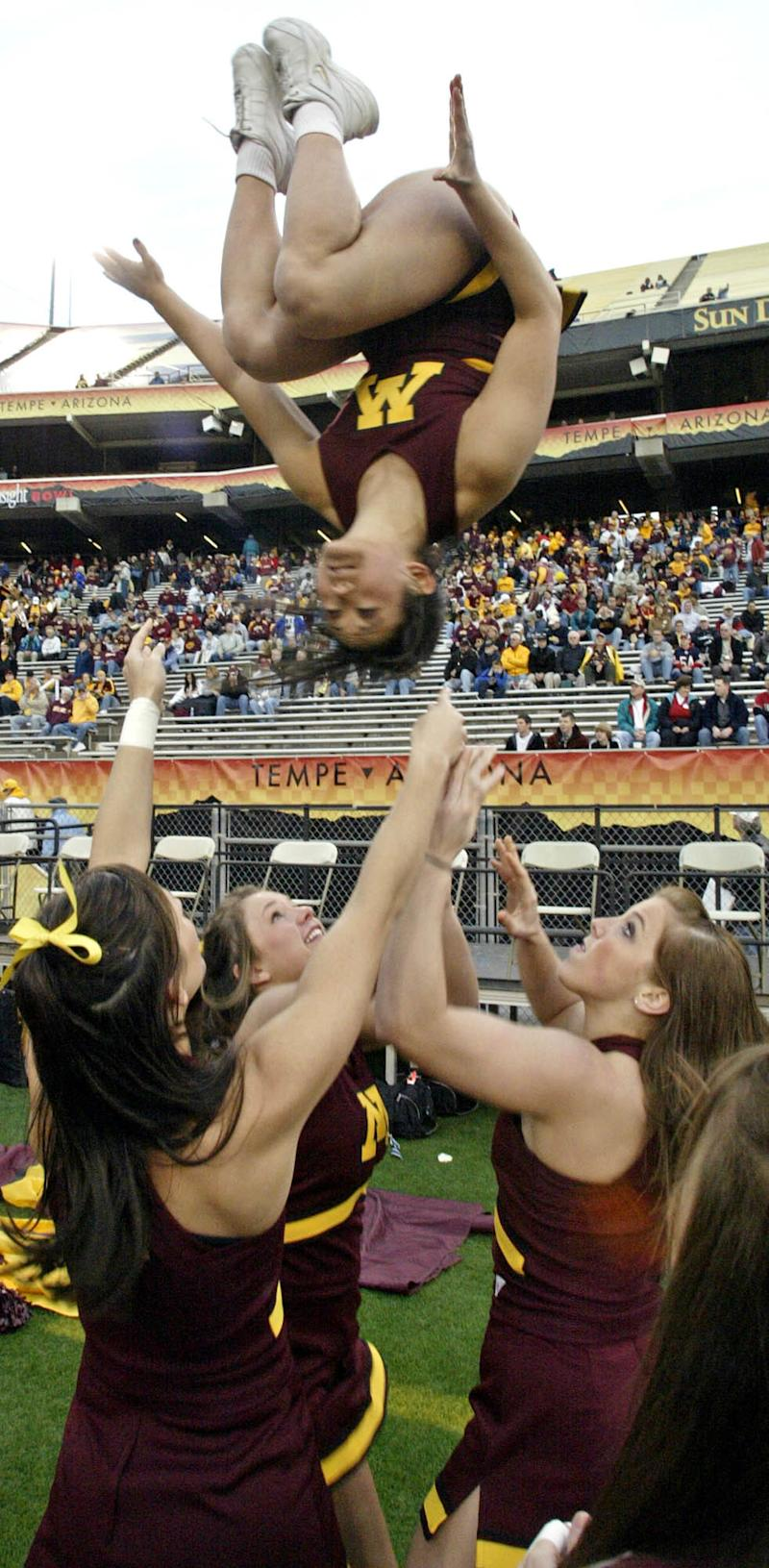MARLIN LEVISON *mlevison@startribune.com 12/29/06 Assign# 107906- Minnesota Gophers vs. Texas Tech in Insight Bowl. Minnesota cheerleaders and marching band get in the spirit of the game with 'basket tosses' on the sideline while the band waves 'cheer sticks' from their stadium seats. IN THIS PHOTO: Cheerleader Katie Lund of Minneapolis is tossed in the air by teammates. (Photo by Marlin Levison/Star Tribune via Getty Images)