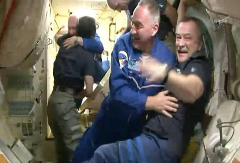 In this frame grab from video provided by NASA, Expedition 39 Soyuz Commander Aleksander Skvortsov, facing, second from right, of the Russian Federal Space Agency, is welcomed aboard the International Space Station by fellow Russian cosmonaut Mikhail Tyurin, right, Thursday, March 27, 2014, after the Soyuz docked. At left, Japanese astronaut Koichi Wakata welcomes Russian cosmonaut Oleg Artemyev, background, through the hatch of the space station. The new crew will stay in orbit for six months. (AP Photo/NASA)