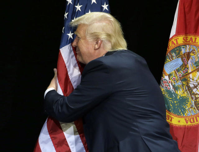 <p>Trump pauses during his campaign speech to hug the American flag, June 11, 2016, in Tampa, Fla. <i>(Photo: Chris O'Meara/AP)</i> </p>