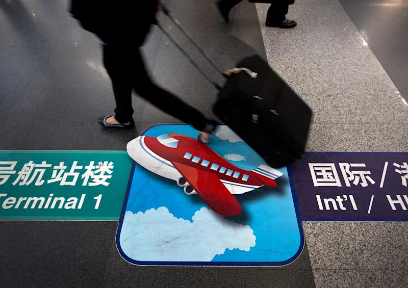 In this Wednesday, Sept. 26, 2012 photo, a passenger carries her luggage past a flight direction sign at the Beijing Capital International Airport in Beijing. From almost none a decade ago, Asia now has more than 50 low cost carriers. The fast growth of no-frills airlines underline surging demand in the region for affordable air travel. But in China, where the government still keeps tight control of the rapidly growing airline industry, three big state-owned carriers dominate, leaving Chinese travelers out of the massive budget airline boom that has swept the region. (AP Photo/Andy Wong)