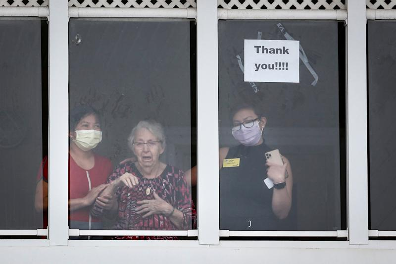 Residents and staff wave to family and friends who came out to show support of those in the McKenzie Towne long term care centre in Calgary on April 2, 2020. (Photo: Jeff McIntosh/THE CANADIAN PRESS)