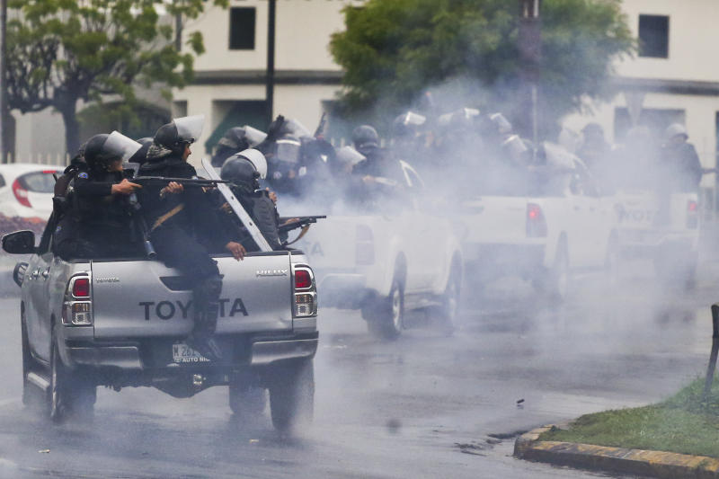 FILE - In this May 28, 2018 file photo, police in riot gear riding on the back of pick-up trucks fire their shotguns towards university students taking part in a protest against Nicaragua's President Daniel Ortega in Managua, Nicaragua. The U.S. Treasury announced sanctions Friday, May 22, 202 against two high-ranking Nicaraguan officials for their support of government crackdowns on protesters. (AP Photo/Esteban Felix, File)