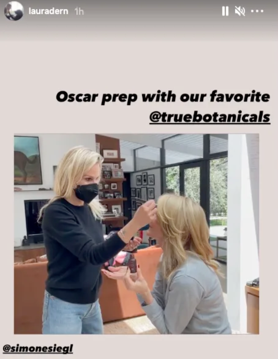 Laura dern holds up a bottle of true botanics oil while her makeup artist finishes her Oscars look