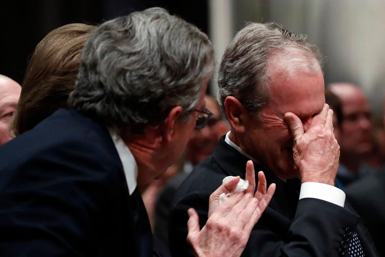 Former President George W. Bush, right, cries after speaking during the state funeral for his father.