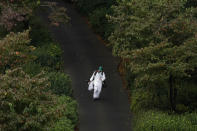 A caddie walks along the sixth hole during the first round of the Masters golf tournament Friday, Nov. 13, 2020, in Augusta, Ga. (AP Photo/Matt Slocum)