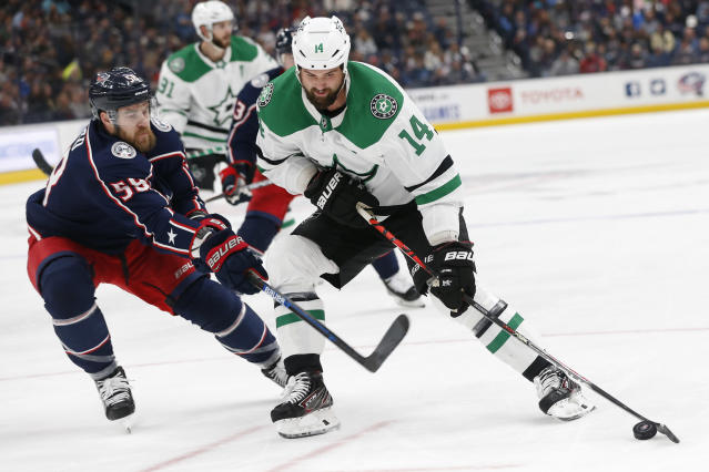 Dallas Stars' Jamie Benn, right, is defended by Columbus Blue Jackets' David Savard during the first period of an NHL hockey game Wednesday, Oct. 16, 2019, in Columbus, Ohio. (AP Photo/Jay LaPrete)