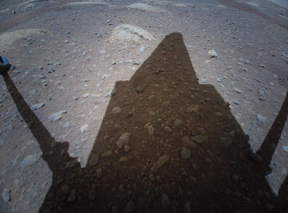 ingenuity helicopter shadow on rocky mars soil