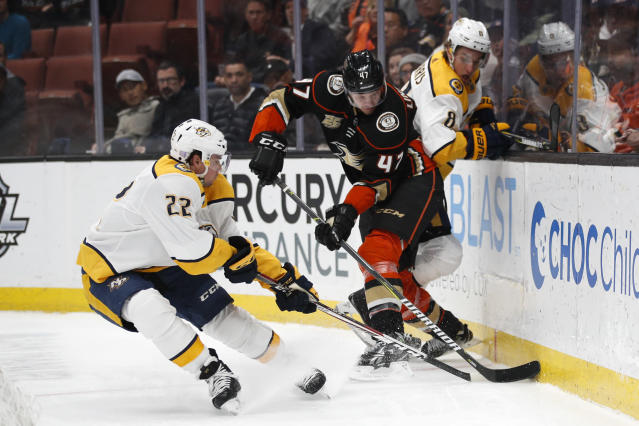 Anaheim Ducks' Hampus Lindholm, center, of Sweden, fights for the puck with Nashville Predators' Kevin Fiala, left, of Switzerland, and Kyle Turris during the first period of an NHL hockey game Monday, Nov. 12, 2018, in Anaheim, Calif. (AP Photo/Jae C. Hong)