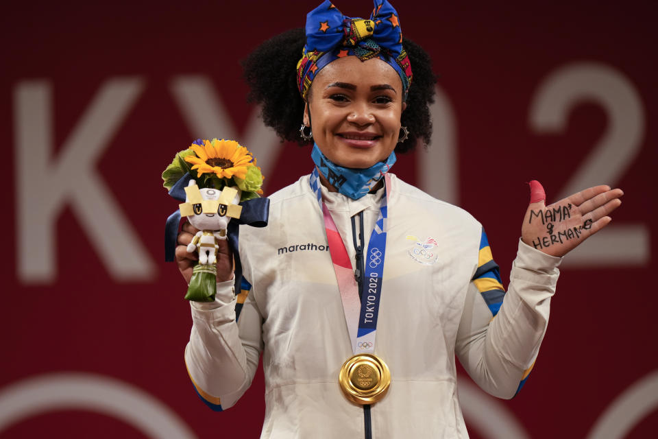 """Neisi Patricia Dajomes Barrera of Ecuador shows off writing on her hand reading in Spanish, """"Mom and brother,"""" after she received the gold medal in women's 76kg weightlifting, at the 2020 Summer Olympics, Sunday, Aug. 1, 2021, in Tokyo, Japan. (AP Photo/Luca Bruno)"""
