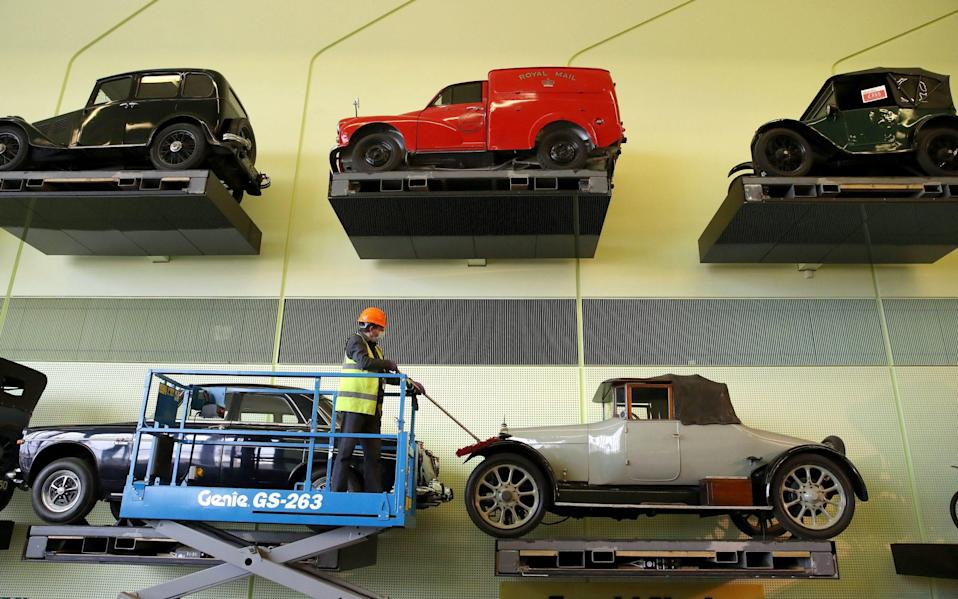 Jacek Wiklo conservator at the Riverside Museum in Glasgow dusts the cars on the car wall ahead of the museum re-opening on Monday as lockdown restrictions in Scotland have begun to gradually ease - Andrew Milligan/PA Wire