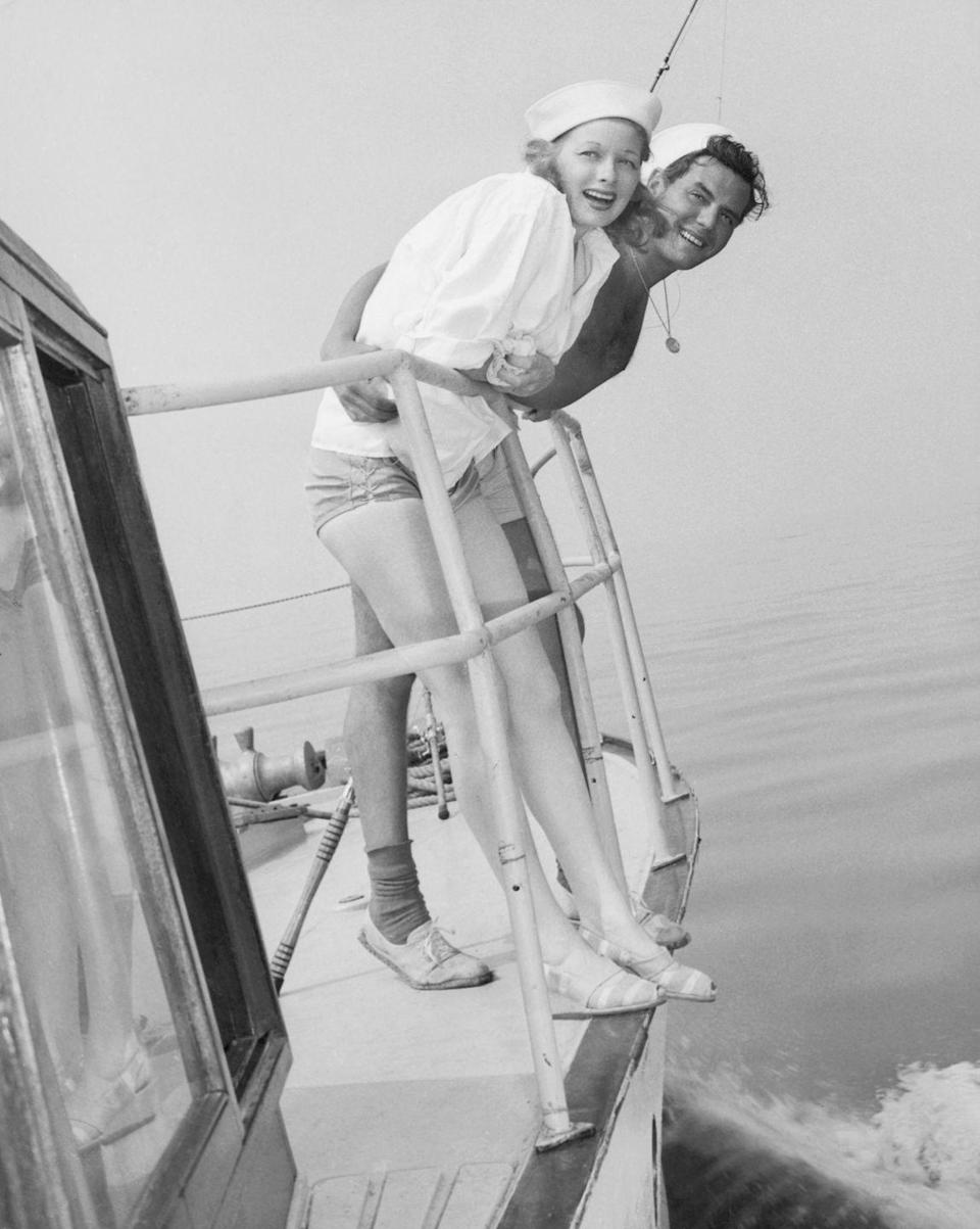 <p>Lucille Ball and Desi Arnaz lean over the railing of a motorboat, while sporting skipper hats and bathing suits. Ball wears an oversized white button-down as a cover-up. </p>