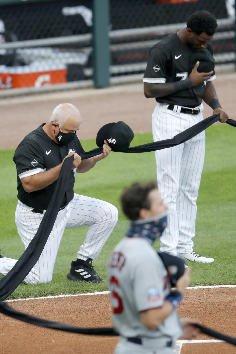 Chicago White Sox manager Ricky Renteria kneels for social justice next to Tim Anderson before a baseball game against the Minnesota Twins, Friday, July 24, 2020, in Chicago. (AP Photo/Charles Rex Arbogast)