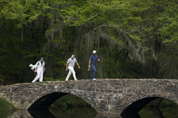 Dustin Johnson, right, and Lee Westwood, of England, walk across the Hogan Bridge during the second round of the Masters golf tournament on Friday, April 9, 2021, in Augusta, Ga. (AP Photo/Charlie Riedel)