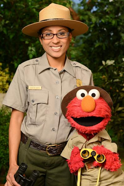 """This undated publicity image released by Sesame Workshop shows Ranger Shalini Gopie with the character Elmo from the children's series """"Sesame Street,"""" during a segment on national parks. A new project has recruited Muppet monsters Elmo and Murray to visit national parks in six short videos that encourage children aged 3 through 5 to experience the great outdoors, wherever it might be, and to apply scientific skills of inquiry to learn about these natural settings. (AP Photo/Sesame Workshop)"""