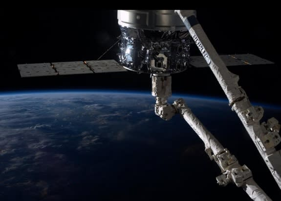 """NASA Astronaut Karen L. Nyberg took this beautiful photo while aboard the International Space Station. """"Sunrise on #Cygnus and #Canadarm2."""" She tweeted on Oct. 6."""