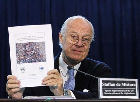 U.N. special representative in Afghanistan De Mistura holds a report during a news conference in Kabul