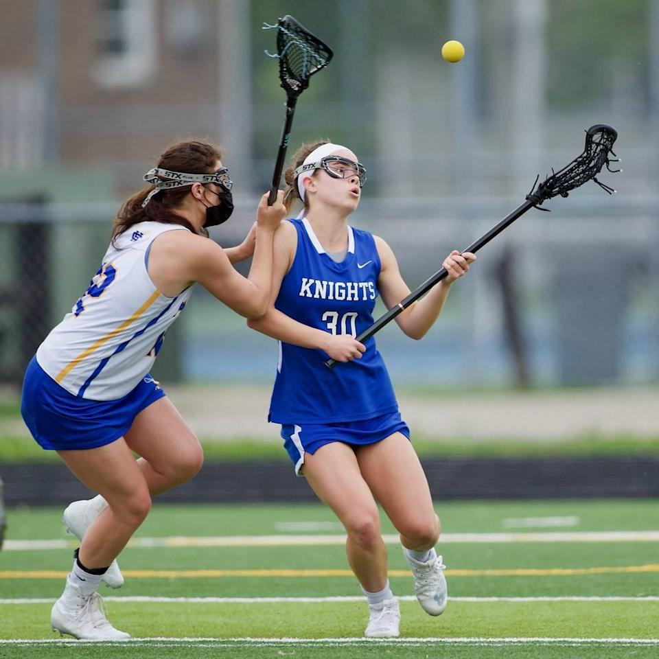 Lexington Catholic's Morgan Cameron battles to cradle the ball against Henry Clay's Tori Sloane during a May 2, 2021 game at Henry Clay. The boys' and girls' teams at Henry Clay each won the 2021 Commonwealth Lacrosse League state championship.