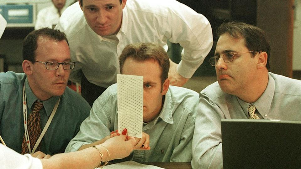 Broward County Election employees, reporters and Judicial Watch members look at ballot papers December 18, 2000