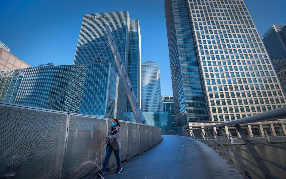 A woman wearing a protective face mask walks in Canary Wharf - Victoria Jones/PA