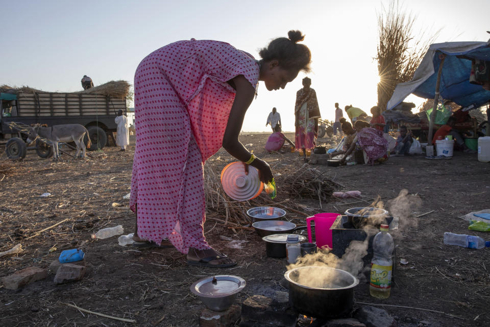 A Tigray refugee woman who fled the conflict in the Ethiopia's Tigray cooks breakfast at Hamdeyat Transition Center near the Sudan-Ethiopia border, eastern Sudan, Thursday, Dec. 3, 2020. Ethiopian forces on Thursday blocked people from the country's embattled Tigray region from crossing into Sudan at the busiest crossing point for refugees, Sudanese forces said.(AP Photo/Nariman El-Mofty)