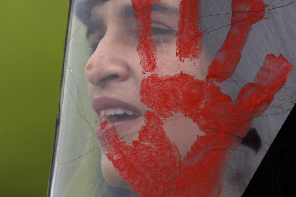 A demonstrator wears a face shield with a red handprint, mimicking blood, to protest Brazilian President Jair Bolsonaro's handling of the deadly coronavirus pandemic in Brasilia, Brazil, Wednesday, Dec. 23, 2020. Protesters also called for the immediate start of COVID-19 vaccinations. (AP Photo/Eraldo Peres)