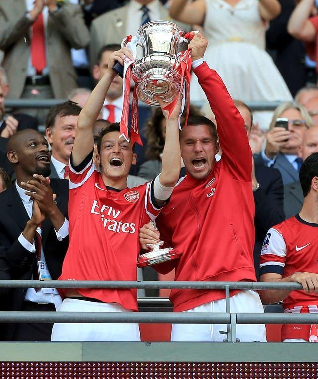 Ozil (left) helped Arsenal win the FA Cup three times (Nick Potts/PA).