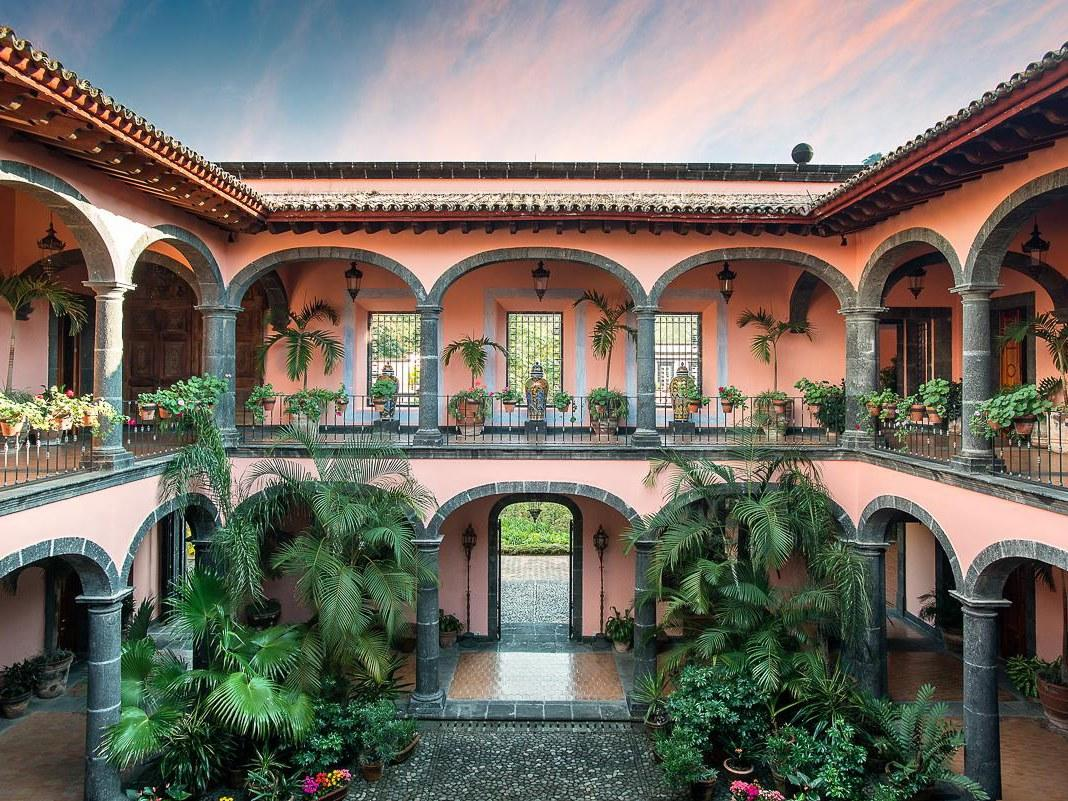 <p><strong>Why did this hotel catch your attention? What's the vibe?</strong> Getting to this pink palace hidden deep in Colima's verdant tropical cloud forest was a feat. And part of the adventure. The colonial coffee plantation offers a slice of Mexican luxury you don't find elsewhere, with Jaguar basalt stone carved canals, pools with volcano views, and breezy loggias and courtyards offering space for all.</p> <p><strong>What's the backstory?</strong> This is an independently owned property and has a sister property on the coast, Cuixmala. Opulent and muy romantico.</p> <p><strong>Tell us all about the accommodations. Any tips on what to book?</strong> Volcanic stone and ceramic floor terrace with big poster beds and fireplaces. French doors open to a terrace, and bright colored textiles remind you you're in Mexico.</p> <p><strong>Drinking and dining—what are we looking at?</strong> Don't come here for tacos. Colima is known for its abundance of vegetables and fruits, like citrus and avocados—many of which are grown on the property's Rancho Jabalí. The more subtle Mexico mountain cuisine steers away form typical Mexican food, and offered less spicy plates of meat. Juices were aplenty.</p> <p><strong>And the service?</strong> Service was spartan, and not necessary to enjoy the stay. It's a pretty straightforward property in terms of what it offers, so it was better to explore and discover the estate than be hand held by staff.</p> <p><strong>What type of travelers will you find here?</strong> I was the only guest while there! It felt like my own dreamy private villa.</p> <p><strong>What about the neighborhood? Does the hotel fit in, make itself part of the scene?</strong> It's very isolated with not much around, except chacalacas and jaguars prowling the cloud forest, so you do want to stay on property and experience what the hotel can do—and watch the volcano puff away from a poolside chair.</p> <p><strong>Is there anything you'd change?</strong> No, it was magic