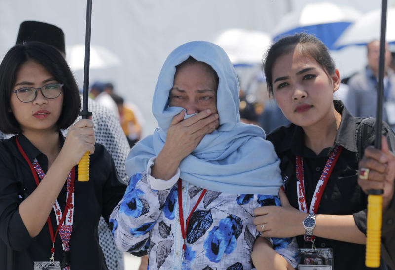 A relative cries during a prayer service for victims in the crashed Lion Air flight 610 aboard an Indonesia Navy ship in the waters where the airplane is believed to have crashed in Tanjung Karawang, Indonesia, Tuesday, Nov. 6, 2018. (AP Photo/Tatan Syuflana)