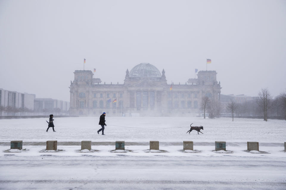 Walkers with dog walk in front of the German parliament, the Reichstag building, during snowfall in Berlin, Germany, Sunday, Feb. 7, 2021. (Christoph Soeder/dpa via AP)