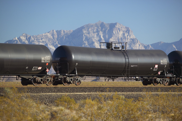 Three tanker cars on a railroad track in front of a mountain view.