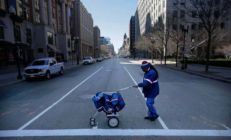 BOSTON, MA - MARCH 18: A USPS letter carrier crosses a quiet Boylston Street with greatly reduced foot and vehicle traffic in Boston on March 18, 2020. Fewer people are out and about as they try to prevent the spread of coronavirus. (Photo by Lane Turner/The Boston Globe via Getty Images)