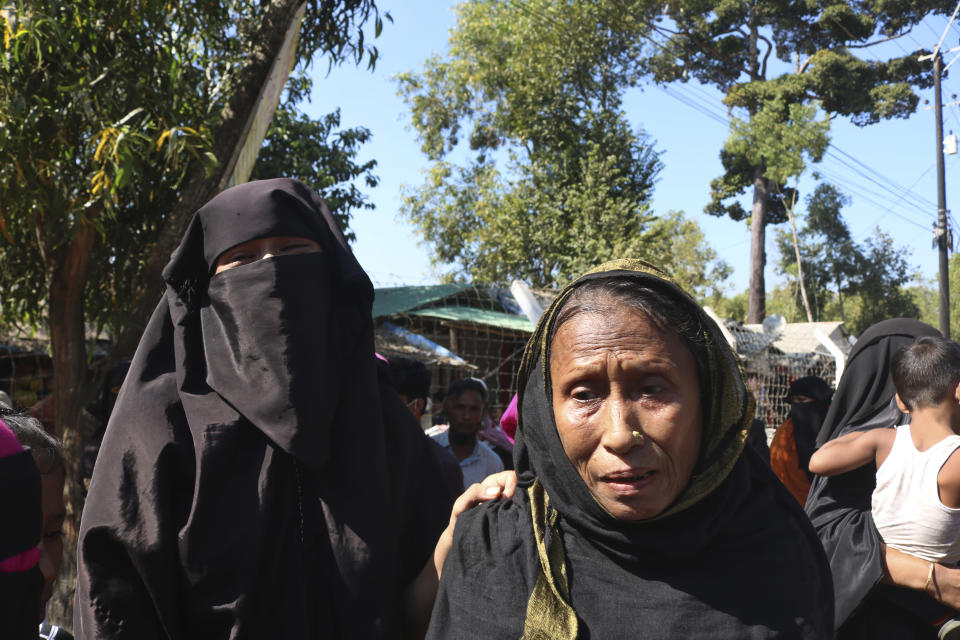 Rohingya refugees who are being moved to an island called 'Bhasan Char' gather outside a transit area where they are temporally housed in Ukhiya, Bangladesh, Thursday, Dec.3, 2020. (AP Photo/ Shafiqur Rahman)