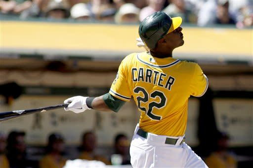Oakland Athletics' Chris Carter watches the flight of his two-run home run, driving in Yoenis Cespedes, in the sixth inning of a baseball game against the Los Angeles Angels in Oakland, Calif., Wednesday, Aug. 8, 2012. (AP Photo/Dino Vournas)