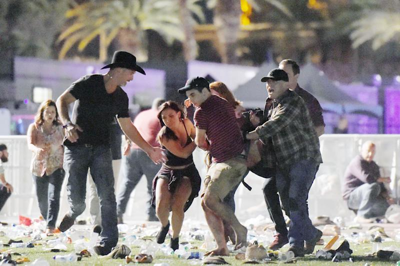 Concert-goers carry a victim to safety after the shooting: Getty