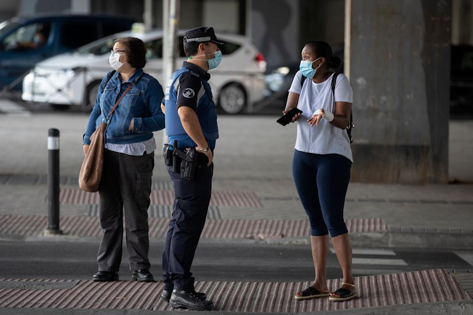 A local police officer talks with a woman at a checkpoint in the Vallecas neighborhood in Madrid, Spain, on Wednesday. (Photo: ASSOCIATED PRESS)