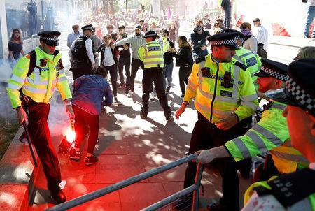 A police officer holds a flare during demonstrations outside Downing Street ahead of the visit by Turkey's President Recep Tayyip Erdogan, in London, Britain, May 15, 2018. REUTERS/Peter Nicholls