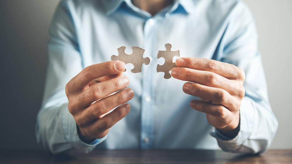 man hand holding two puzzle.