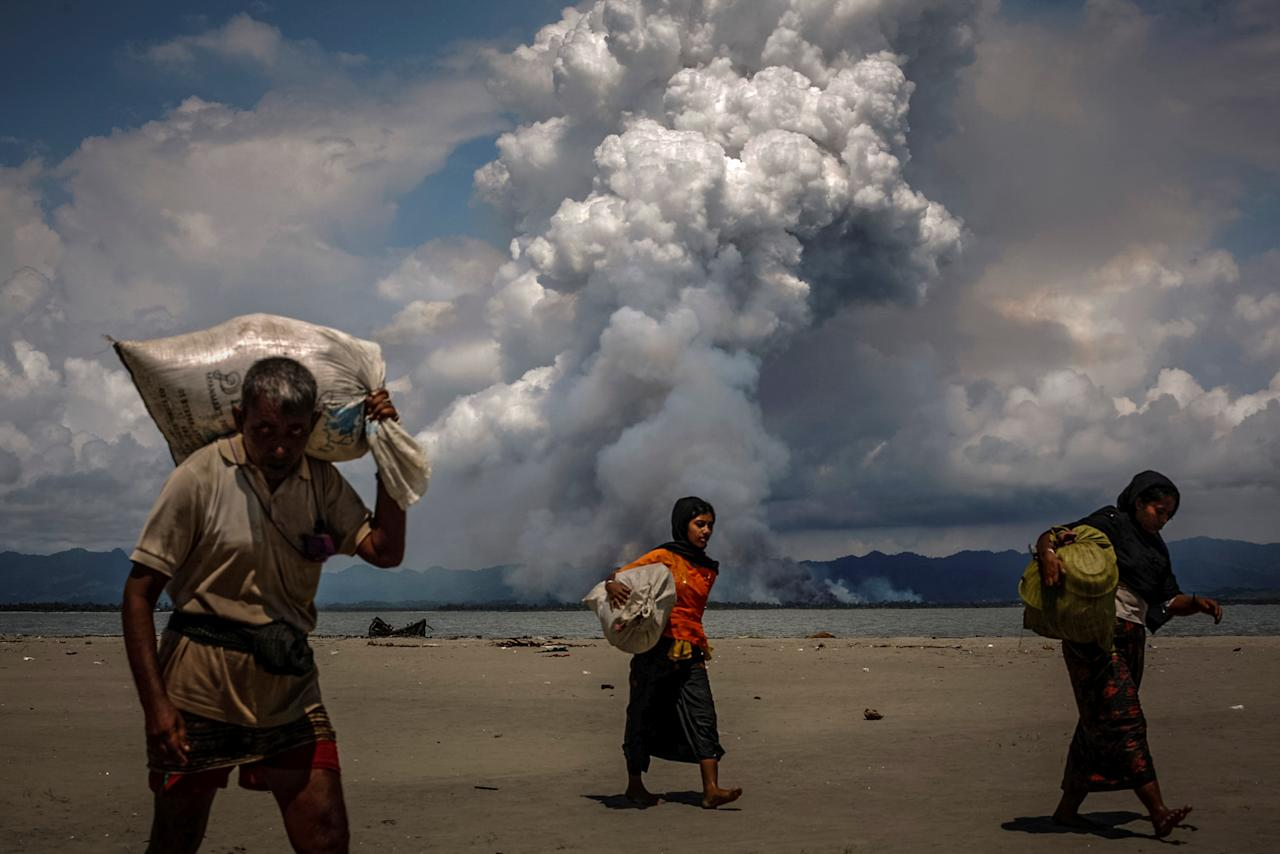 <p>Smoke is seen on the Myanmar border as Rohingya refugees walk on the shore after crossing the Bangladesh-Myanmar border by boat through the Bay of Bengal, in Shah Porir Dwip, Bangladesh, Sept.11, 2017. (Photo: Danish Siddiqui/Reuters) </p>