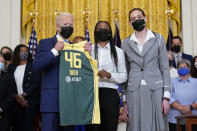 President Joe Biden, left, poses for a photo with Seattle Storm's Jewell Loyd, center, and Breanna Stewart, right, during an event in the East Room of the White House in Washington, Monday, Aug. 23, 2021, to celebrate their 2020 WNBA Championship. (AP Photo/Susan Walsh)