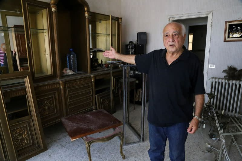 Maurice Srour gestures as he stands at his home which was damaged due to the massive explosion at Beirut's port area