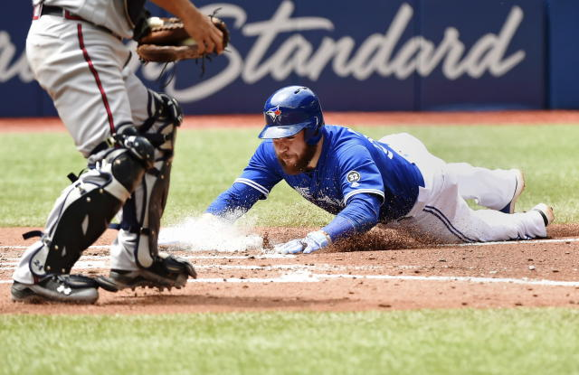 Toronto Blue Jays catcher Russell Martin scores against the Atlanta Braves on a sacrifice fly by Toronto Blue Jays' Aledmys Diaz during the fourth inning of a baseball game in Toronto, Wednesday, June 20, 2018. (Nathan Denette/The Canadian Press via AP)