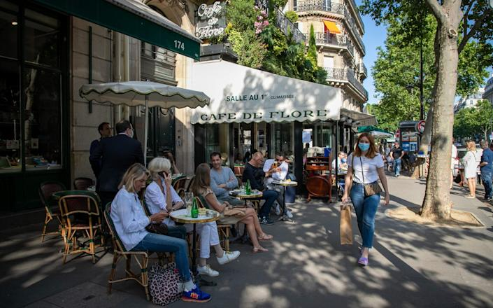 People have drinks at the terrace of 'Cafe de Flore' in the Latin Quarter district as bars and restaurants reopen after two months of nationwide restrictions due to the coronavirus outbreak - Marc Piasecki/Getty Images Europe