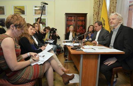 WikiLeaks founder Julian Assange listens as Ecuador's Foreign Affairs Minister Ricardo Patino speaks during a news conference at the Ecuadorian embassy in London