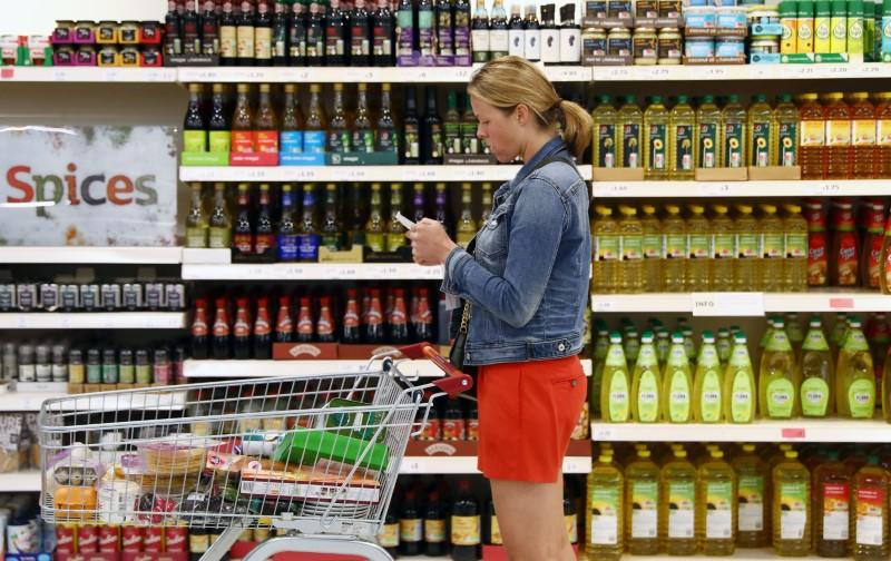 A shopper pushes a trolley in a supermarket in London