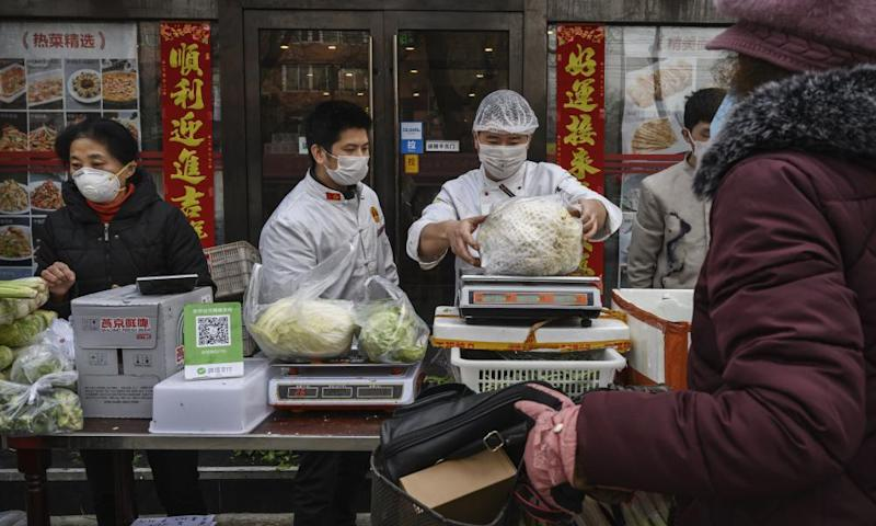 Chinese vendors wear protective masks as they sell vegetables in the street during the Chinese New Year holiday