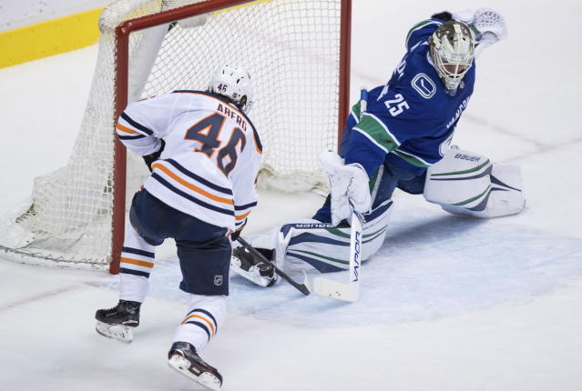 Vancouver Canucks goaltender Jacob Markstrom (25) stops Edmonton Oilers left wing Pontus Aberg (46), both of Sweden, during the second period of an NHL hockey game Thursday, March 29, 2018, in Vancouver, British Columbia. (Darryl Dyck/The Canadian Press via AP)