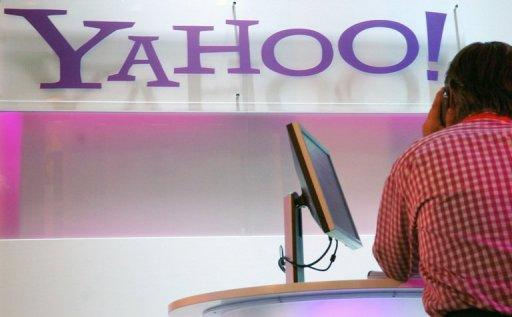 A visitor sits next to a laptop near the logo of Yahoo at a trade fair in Germany. Facebook and Yahoo! announced Friday a new advertising partnership as the two tech giants settled a court dispute over patents