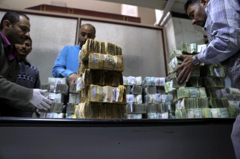 Employees count bundles of newly issued Yemeni Riyal bank notes at the Central Bank of Yemen in Sanaa