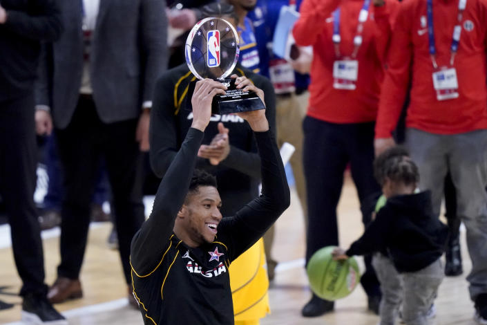 Milwaukee Bucks forward Giannis Antetokounmpo hols up the trophy after basketball's NBA All-Star Game in Atlanta, Sunday, March 7, 2021. (AP Photo/Brynn Anderson)